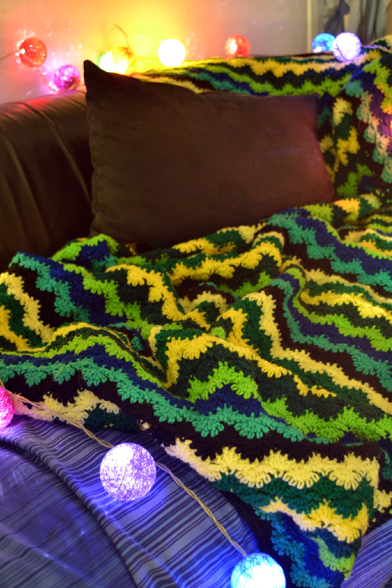 crochet blanket on sofa surrounded by colourful lights